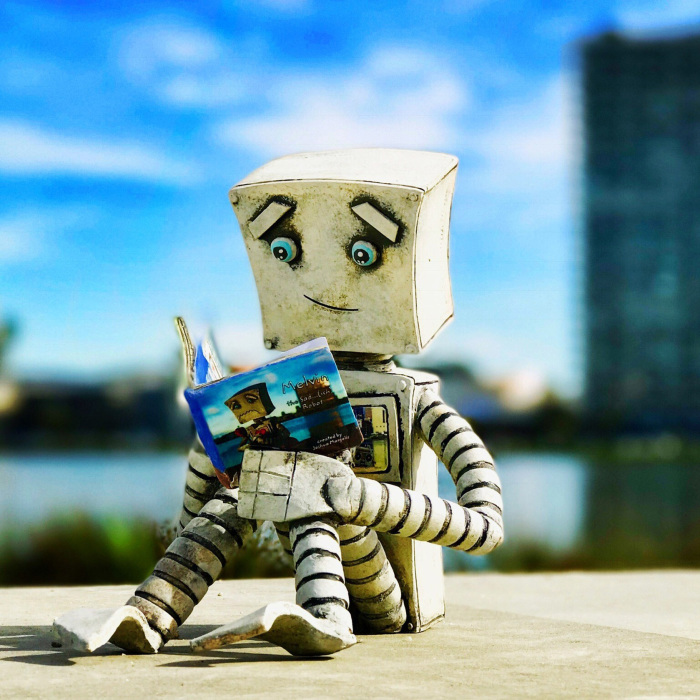 I Photographed My Clay Robot Melvin, Reading A Copy Of His New Book, Melvin The Sad…(ish) Robot