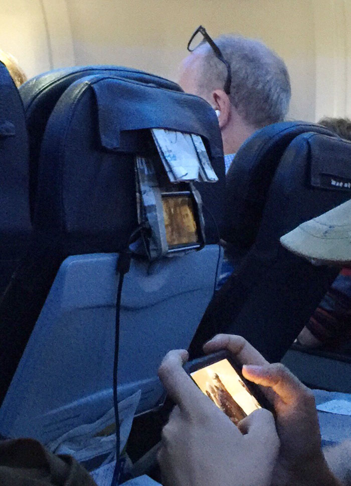 This Guy On Plane Folded His Newspaper To Make A Phone Holder
