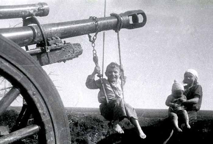 Russian Child Plays On Homemade Swing Made On A German Cannon Left Behind, 1944