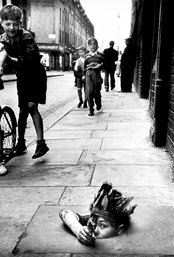 A Young Boy Wearing An Indian Headdress Hides In A Coal Hole And Takes Aim With A Toy Pistol, London, 1954