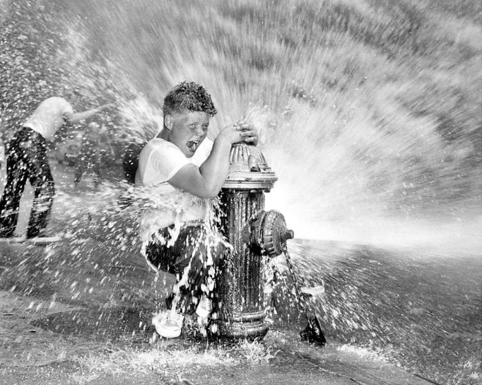 Youngster Playing In Water From Fire Hydrant. Police Are Waging Campaign Against Indiscriminate Opening Of Hydrants Since It Reduces Water Pressure And Poses A Threat To Fire Fighters, New York, 1959
