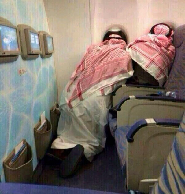 Two Saudi Old Men Peering Out The Windows Of A Plane On Their First Time Flying