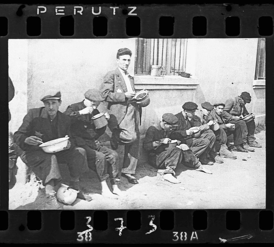 "1940-1944: ""Soup For Lunch"" (Group Of Men Alongside Building Eating From Pails)"