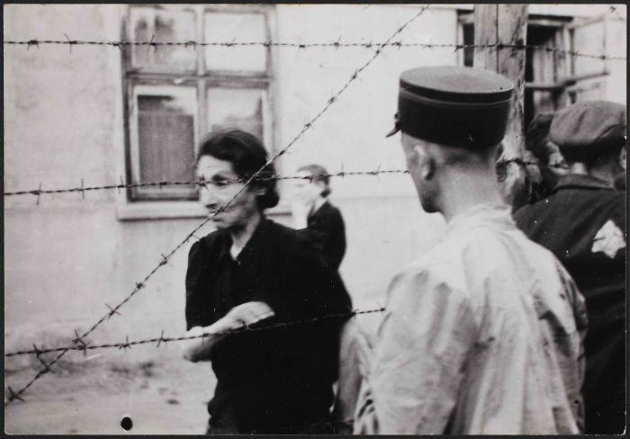 1942: Policía con una mujer tras la alambrada del gueto