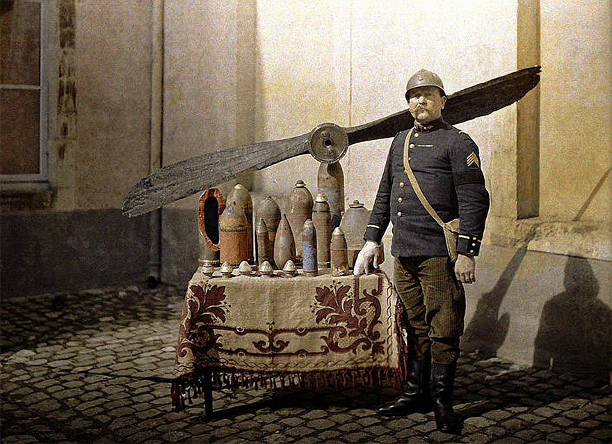 A French Soldier Stands Next To A Table With German Shells And An Aircraft Propeller, Along The Western Front In Reims, 1917