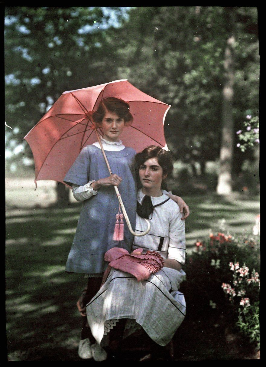 The Younger Girl Stands Beside Her Sister Holding A Pink Parasol. The Older Girl Rests Her Bonnet On Her Lap, 1908