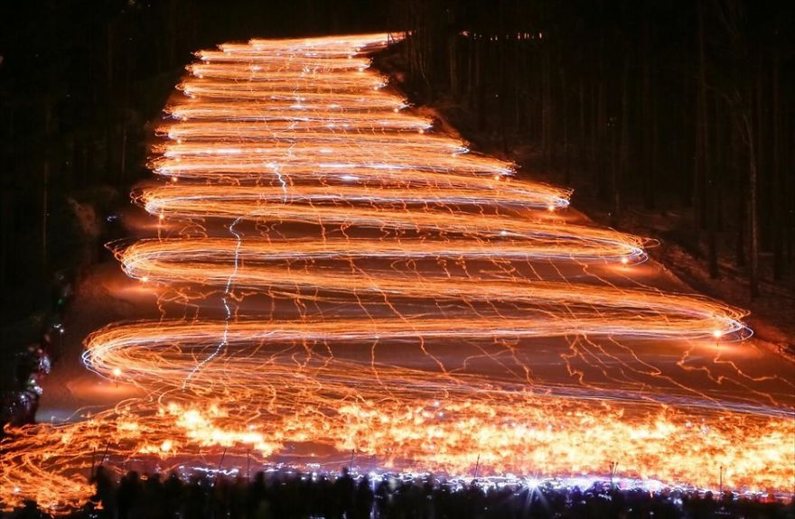 Long Exposure Of Hundreds Of Skiers Holding Flashlights
