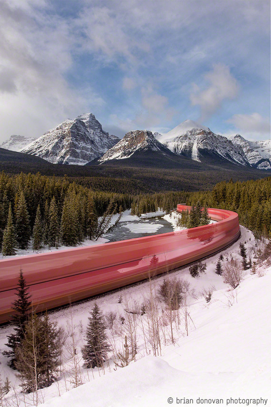 A Long Exposure Photo Of A Train Roaring Through The Canadian Rockies