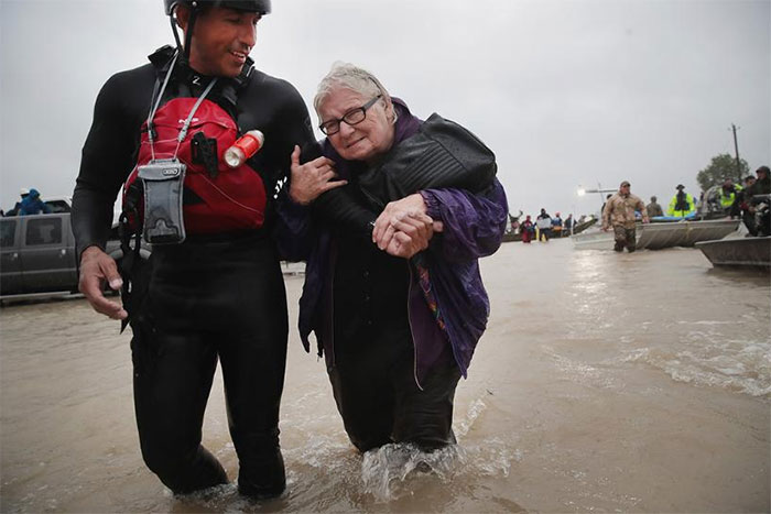 Barb Davis, 74. Is Helped To Dry Land After Being Rescued From Her Flooded Neighborhood After It Was Inundated With Rain Water, Remnants Of Hurricane Harvey