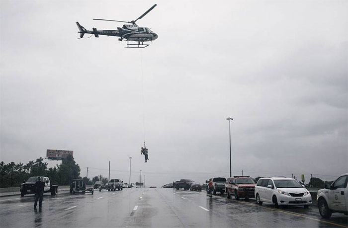 A Helicopter Lifts A Person During Evacuation Of Houston's Meyerland Area