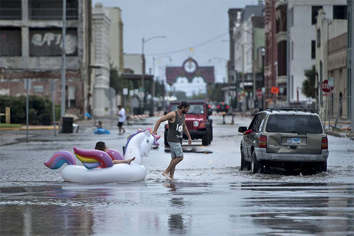People Make Their Way Down Partially Flooded Roads In Galveston, Texas