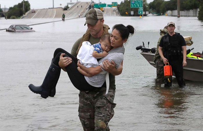 Houston Police SWAT Officer Daryl Hudeck Carries Catherine Pham And Her 13-Month-Old Son Aiden After Rescuing Them From Their Home Surrounded By Floodwaters From Tropical Storm Harvey In Huston