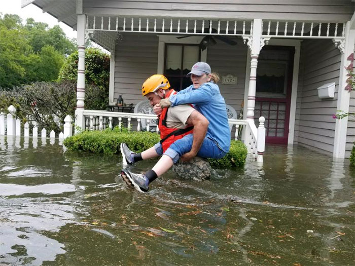 A Texas National Guard Soldier Carries A Woman On His Back As They Conduct Rescue Operations In Flooded Areas Around Houston