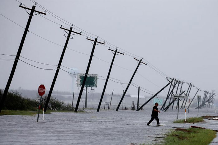 A Man Walks Through Floodwaters And Onto The Main Road After Surveying His Property