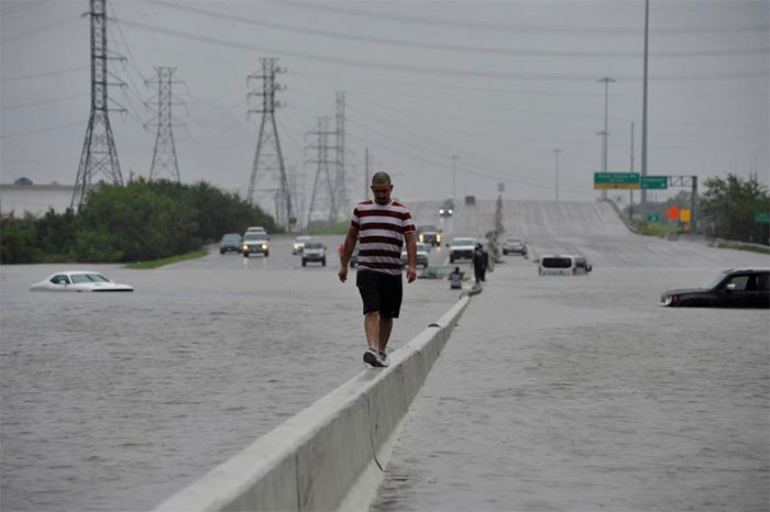A Stranded Motorist Escapes Floodwaters On Interstate 225 In Houston, Texas