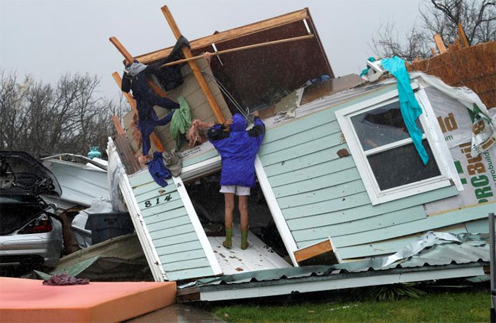 A Woman Uses A Coat Hanger To Try And Retrieve An Item From A Destroyed House In Fulton