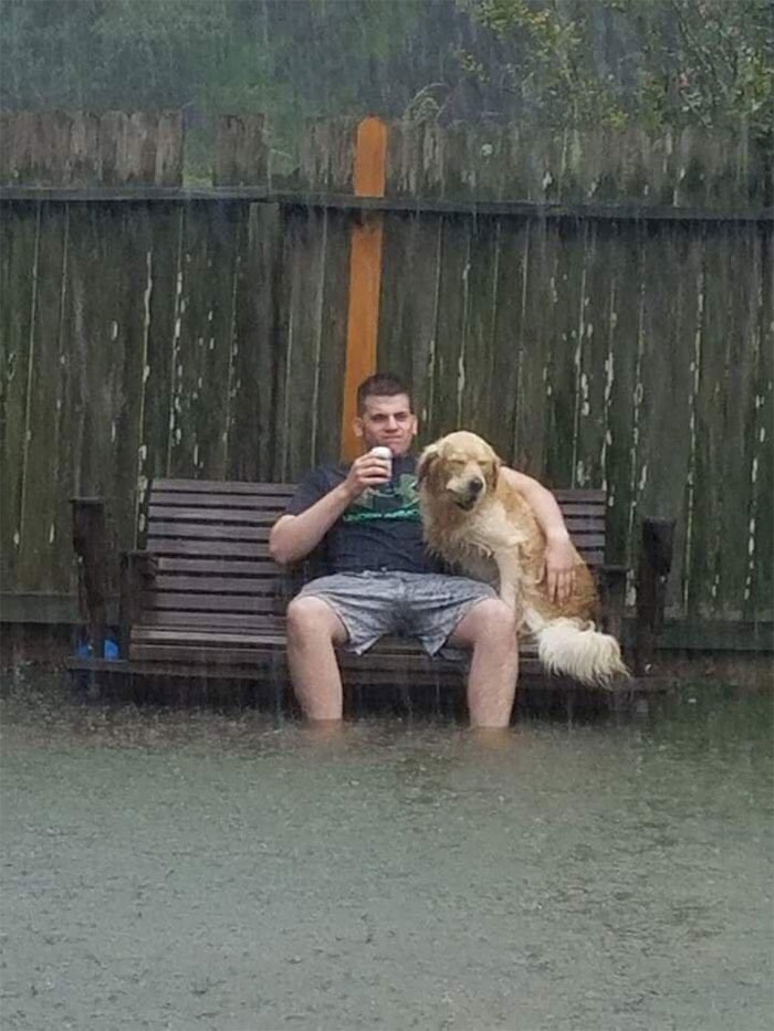Man Sits On Bench With His Dog During Hurricane Harvey