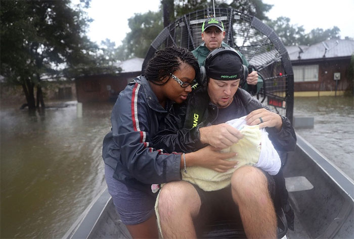 Shardea Harrison Looks At Her 3-week-old Baby, Sarai, As Dean Mize, Right, And Jason Legnon Use An Airboat To Rescue Them From Their Home In Houston