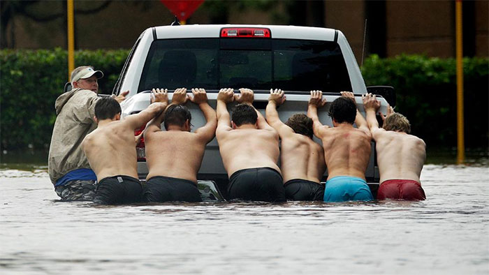 People Push A Stalled Pickup To Through A Flooded Street In Houston