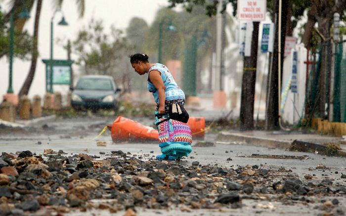 A Woman Pulls A Travel Case On A Rock Scattered Road In The Aftermath Of Hurricane Irma In Fajardo, Puerto Rico