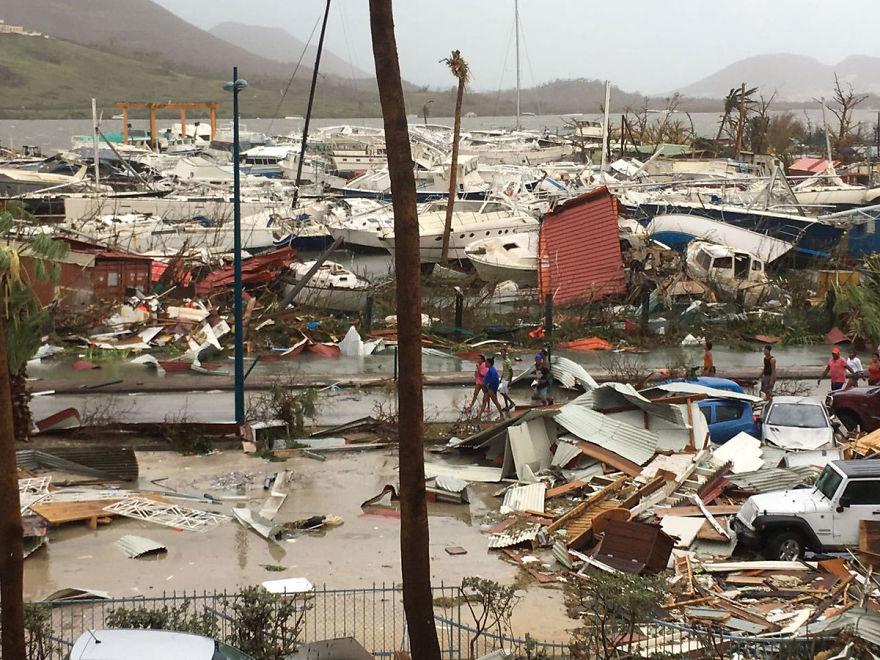 Местные жители прогуливаются по руинам гавани на острове Сен-Мартен после того, как ураган покинул его в руинах