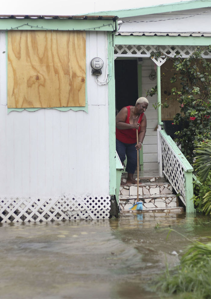 A Woman Pushes Out Floodwaters On Her Property After The Passing Of Hurricane Irma, In St. John's, Antigua