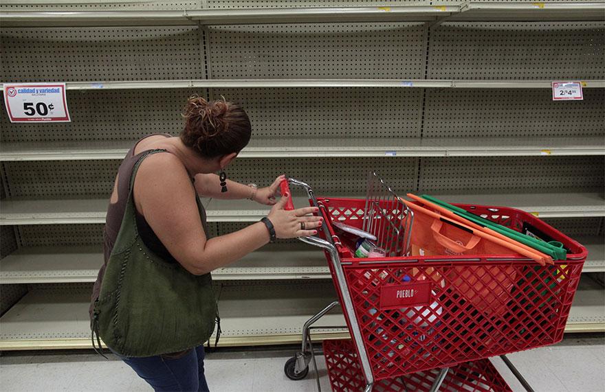 Женщина смотрит на пустые полки, которые обычно заполняются бутылками воды После того, как губернатор Пуэрто-Рико Рикардо Росселло объявил чрезвычайное положение в Сан-Хуане, Пуэрто-Рико