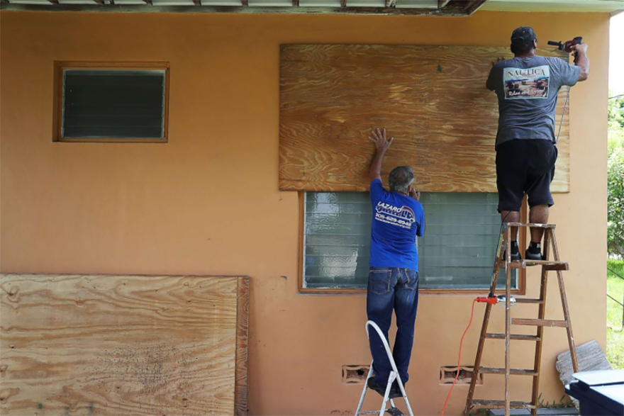 People Put Up Shutters As They Prepare A Family Member's House For Hurricane Irma