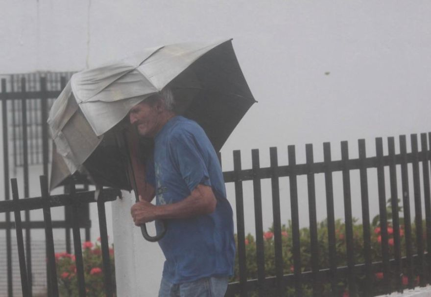 A Man Carrying An Umbrella Walks On A Street In Puerto Rico