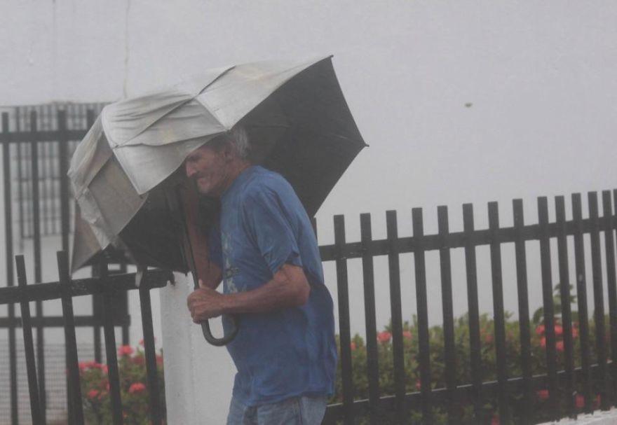 Человек, несущий зонтик, ходит по улице в Пуэрто-Рико