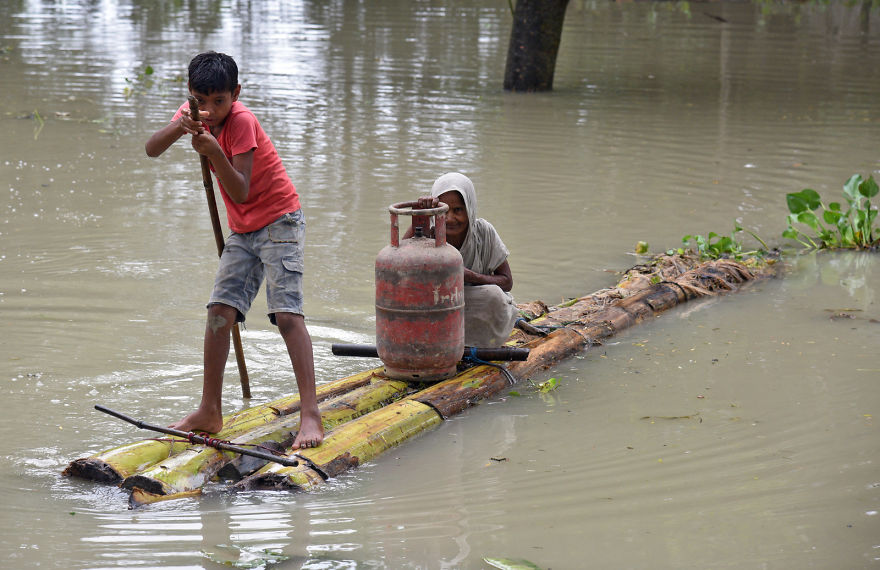 A Boy Rows A Makeshift Raft As He Transports A Woman And A Cooking Gas Cylinder Through The Flood Waters In Assam, India