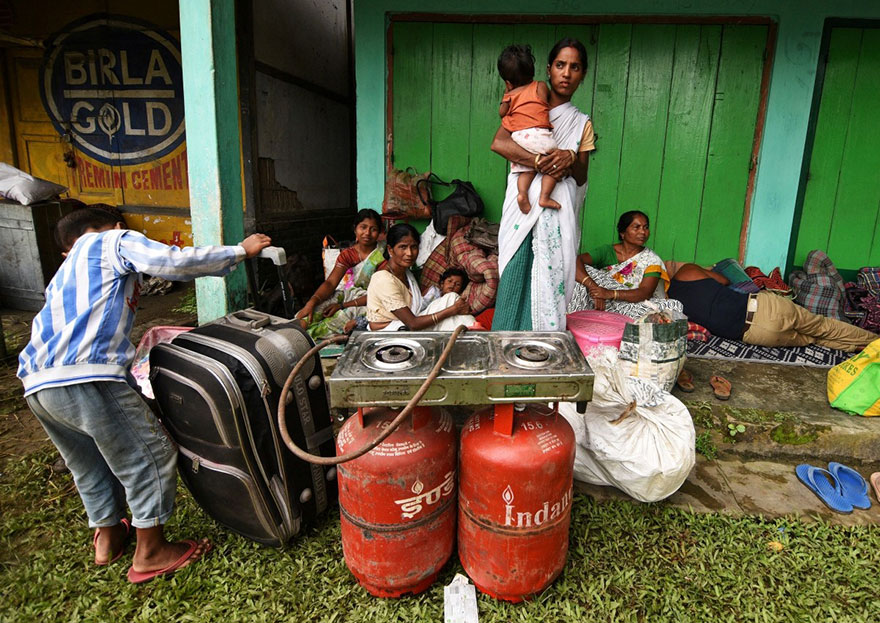 Flood Affected Families Take Shelter In Front Of A Shop And Wait For Relief Material In Jakhalabandha Area In Nagaon District, In The Northeastern State Of Assam, India