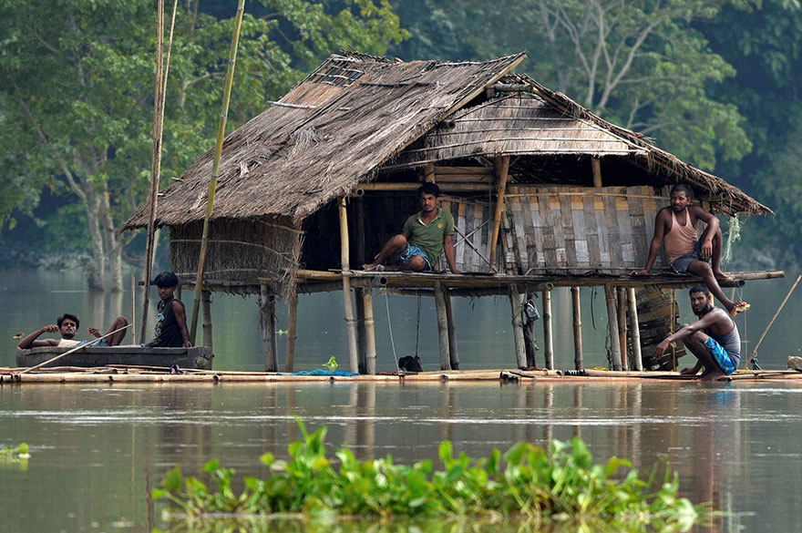 Villagers Take Shelter In A Partially Submerged House Following Floods At Baghmari Village In Nagaon District, In The Northeastern State Of Assam, India