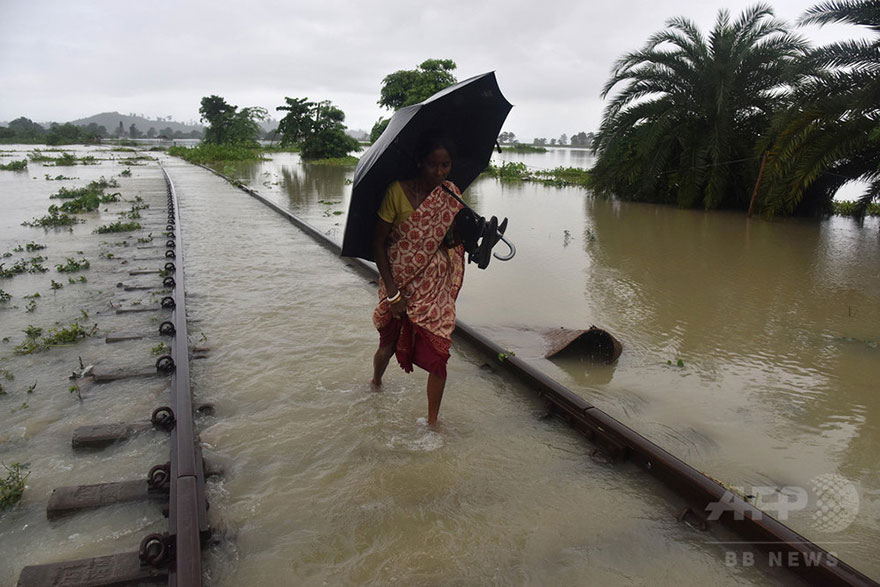 An Indian Villager Walks Along A Submerged Railway Track In The Flood-affected Jakhalabandha Area In Koliabor