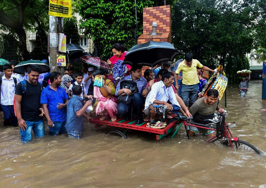 Bangladeshi Commuters Use A Rickshaw To Cross A Flooded Street In Dhaka