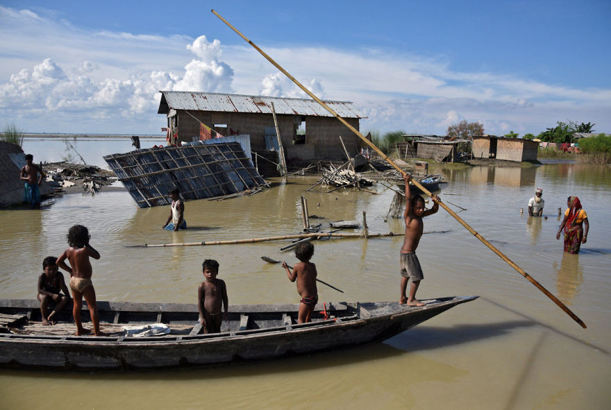 Children Row A Boat As They Pass Through Damaged Houses At A Flood-affected Village In Morigaon District In The Northeastern State Of Assam, India