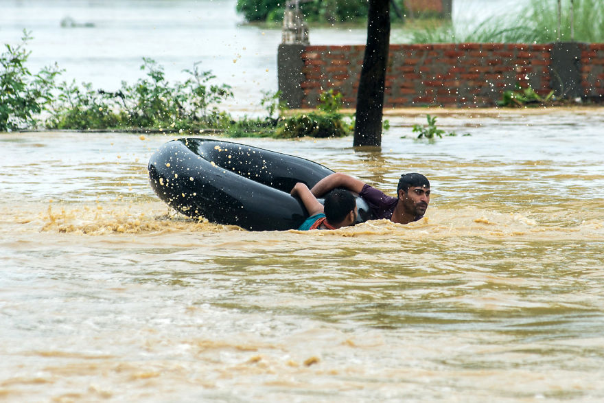 Nepalis Swim With A Rubber Ring In A Flooded Area In Parsa District