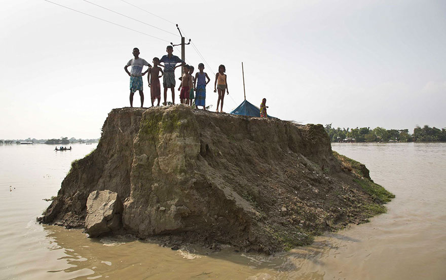 Flood-Affected Villagers Wait For Relief Material On What's Left Of A Road Washed Away By Floodwaters In Morigaon District, East Of Gauhati, Northeastern State Of Assam