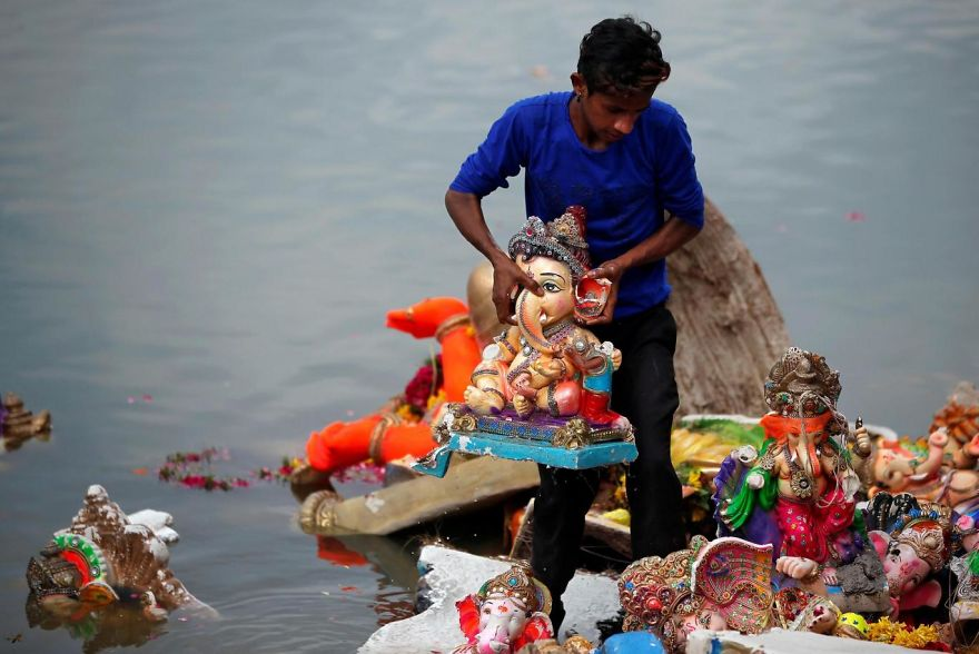 A Man Holds An Idol Of The Hindu God Ganesh, The Deity Of Prosperity, After It Was Immersed In The Waters Of The Sabarmati River