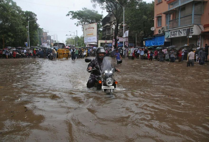 A Man Rides His Motorbike Through A Water-logged Road During Rains In Mumbai