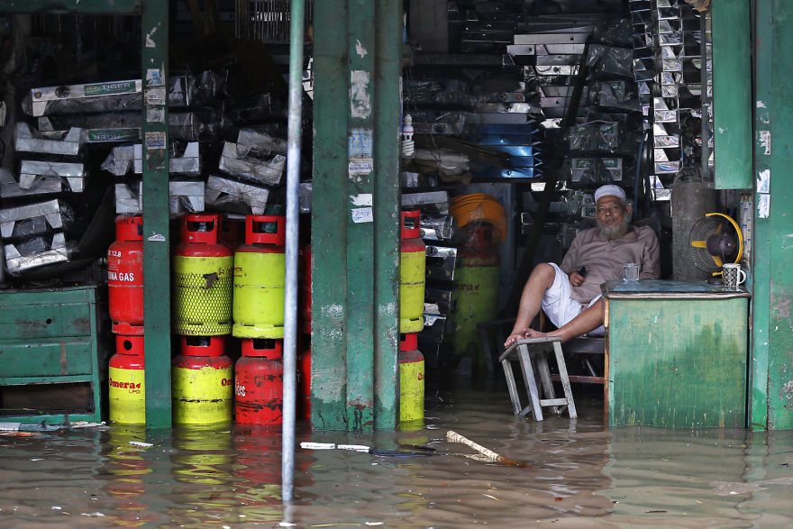 A Bangladeshi Man Sits In His Flooded Shop After Heavy Rain In Dhaka