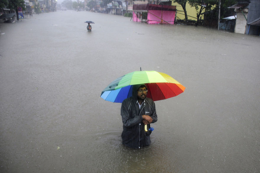 A Man Walks Through A Flooded Street During A Heavy Downpour In The Northeastern Indian State Of Tripura