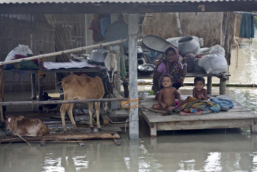 Flood Victims Wait For Relief Supplies In A Village East Of Gauhati In The Northeastern Indian State Of Assam