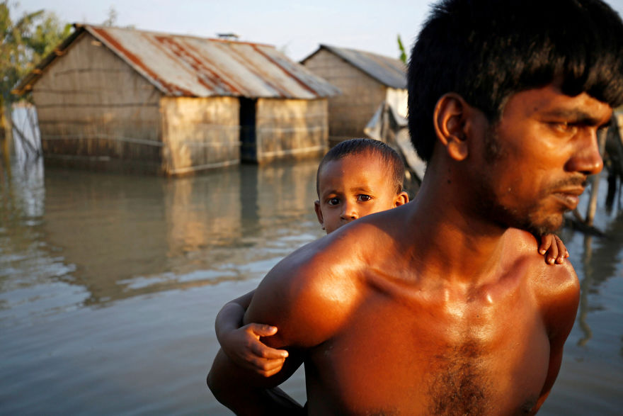 A Child And His Father Walk Through A Flooded Area In Bogra, Bangladesh