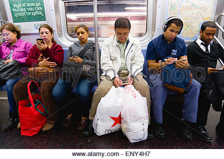 usa-new-york-queens-seated-subway-passengers-on-the-e-train-all-using-eny4h7.jpg