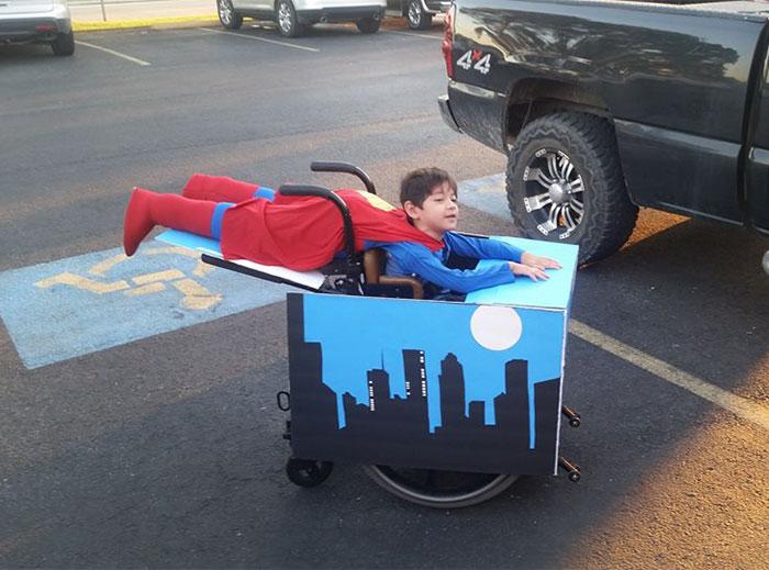 Superman volando, con una silla de ruedas