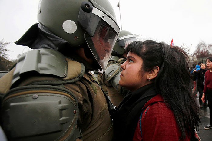 A Demonstrator Faces Down A Riot Policeman During A Pro Democracy Protest In Santiago, Chile, 11 September 2016