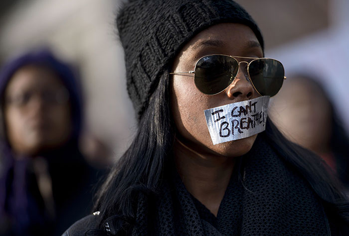 A Woman Listens To A Rally With Her Mouth Taped Shut During The 'Justice For All' March In Washington, Dc, 13 December 2014