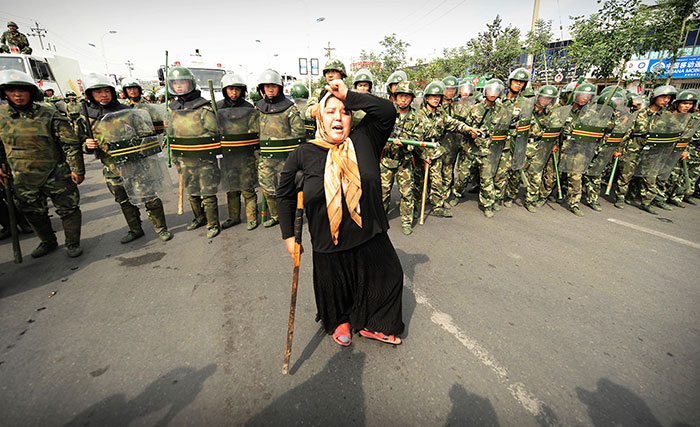 Chinese Riot Police Watch A Muslim Ethnic Uighur Woman Protest In Urumqi In China's Far West Xinjiang Province Following A Third Day Of Unrest, 7 July 2009