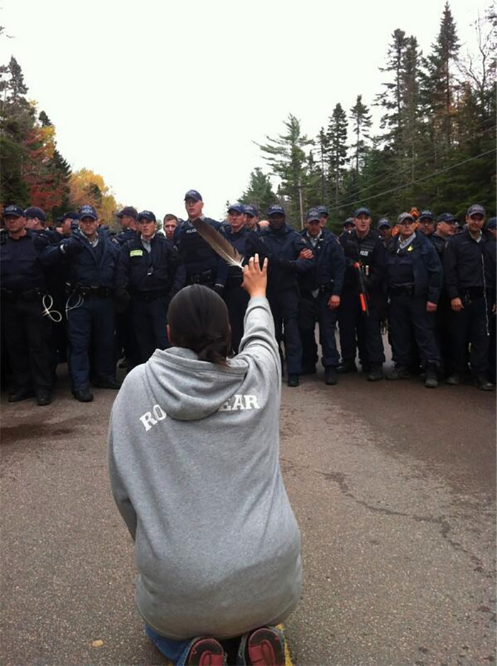 A Woman Kneels Down And Holds Up A Feather While Facing Police Moving In To Break Up Anti-Fracking Protesters In New Brunswick, October 2013